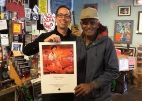 Cat Head owner Roger Stolle and Robert Bilbo Walker holding illustration by Nicki Wambolt